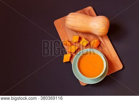 Pumpkin Cream Soup In Bowl,  Butternut Squash And Pumpkin Pieces On Cutting Board On Dark Background