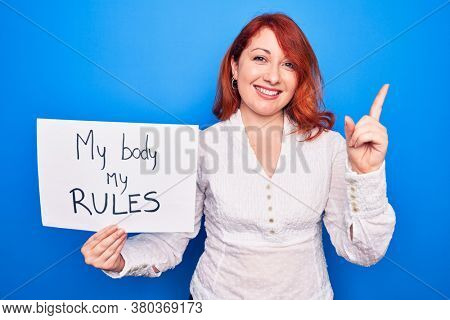 Young redhead woman asking for women rights holding paper with my body my rules message smiling happy pointing with hand and finger to the side