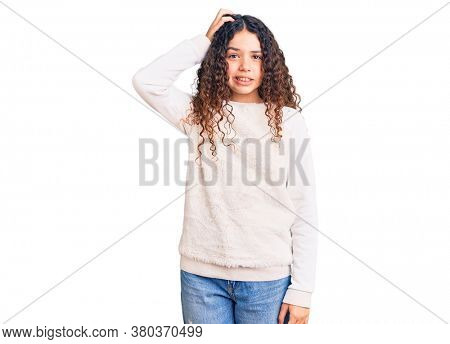 Beautiful kid girl with curly hair wearing casual clothes confuse and wonder about question. uncertain with doubt, thinking with hand on head. pensive concept.