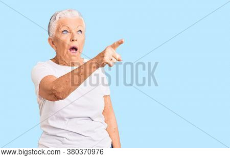 Senior beautiful woman with blue eyes and grey hair wearing casual white tshirt pointing with finger surprised ahead, open mouth amazed expression, something on the front