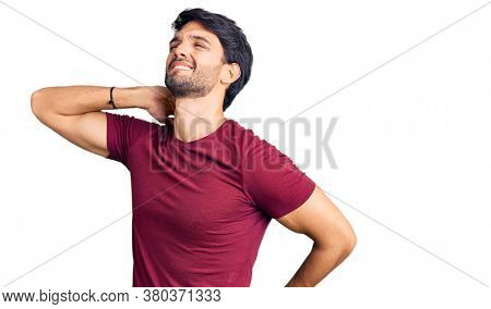 Handsome hispanic man wearing casual clothes suffering of neck ache injury, touching neck with hand, muscular pain