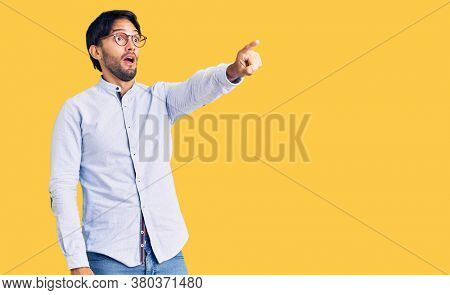 Handsome hispanic man wearing business shirt and glasses pointing with finger surprised ahead, open mouth amazed expression, something on the front