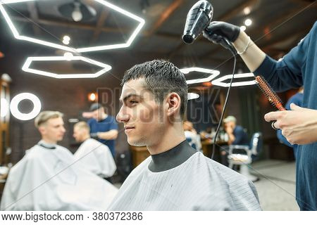 Working Process. Side View Of A Barber Drying The Hair Of A Handsome Guy In The Modern Barber Shop.