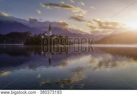 Wonderful Morning Landscape With Calm Lake And Colorful Sky Under Sunlight In Slovenia. Sunset Over