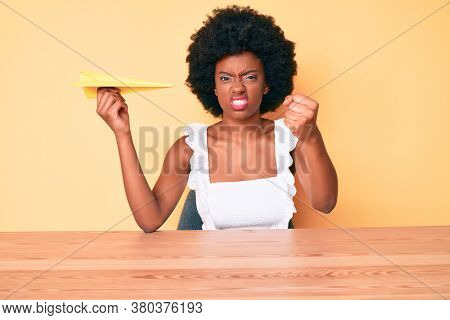 Young african american woman holding paper airplane annoyed and frustrated shouting with anger, yelling crazy with anger and hand raised