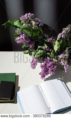 Still Life Of Bright Branch Of Lilac With Books And Open Diary On White Table On Grey Curtains Backg