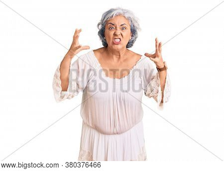 Senior woman with gray hair wearing bohemian style shouting frustrated with rage, hands trying to strangle, yelling mad