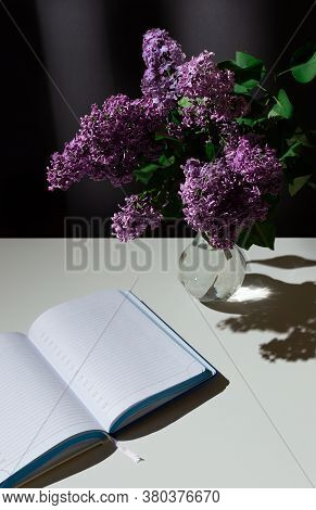Still Life Of Bright Branch Of Lilac In The Glass Vase With Open Diary On White Table On Grey Curtai