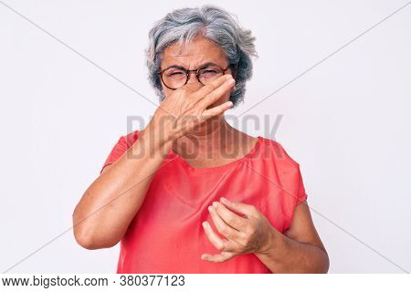 Senior hispanic grey- haired woman wearing casual clothes and glasses smelling something stinky and disgusting, intolerable smell, holding breath with fingers on nose. bad smell
