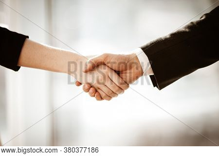 Successful business concept. Young businesswoman and businessman shake hands closeup after signing partnership cooperation contract in office. Two managers man and woman teamwork indoors