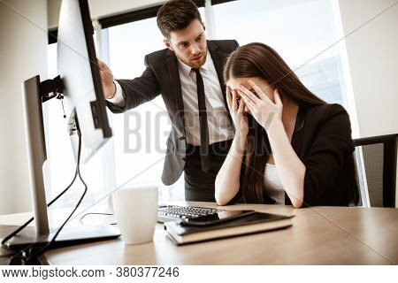 Conflict, crisis and dismissal at work. Young businessman yells at subordinate female assistant after her failure. Businessman points at monitor and fires worker. Resolving a serious work problem