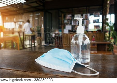Bottle Of Hand Sanitizer Gel Alcohol And Medical Face Mask On Wooden Table With Blurry Coffee Shop B