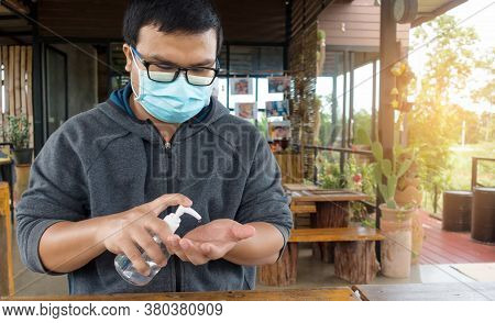 Thailand Man Wearing Medical Face Mask Using Hand Sanitizer In Coffee Shop. Man Sitting In Coffee Sh
