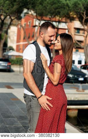 Love Story Outdoors In Summer. An Attractive Young Couple In Love In A Hug. Beautiful Girl In A Long