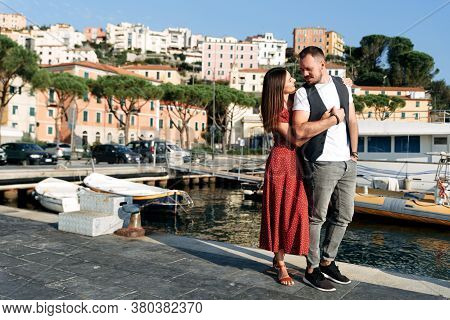 A Couple In Love Walk Happily In A Mediterranean Town. A Guy With A Beard In Casual Clothes, A Girl