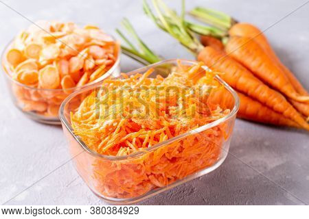 Frozen Grated Carrots In A Glass Container On A Light Background. Frozen Vegetables