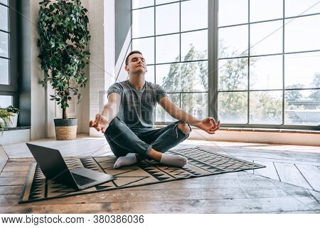 Pleased Caucasian Relaxed Student Sits Crossed Legs On Floor Near Opened Laptop, Tries To Have Break