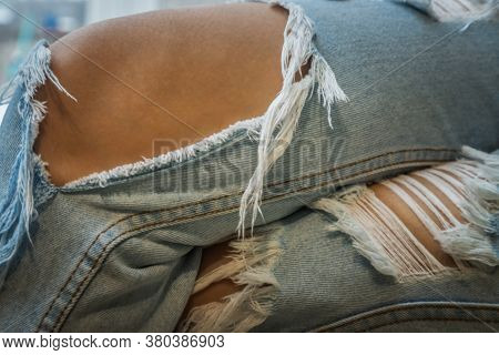 Close Up Of Brown Skin In Distressed Jeans Torn At The Knee. Young Fashionable Asia Woman's Legs In
