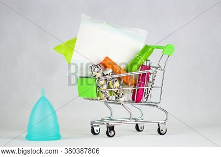 Blue Menstrual Cup And Sanitary Napkins And Tampons In Shopping Cart.menstrual Cup - A Modern Aid Du