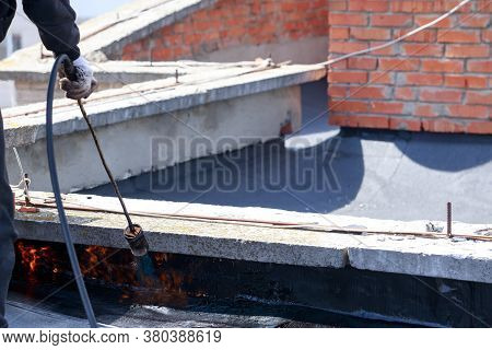 Gas Burner With Fire On The Background Of Roofing Material