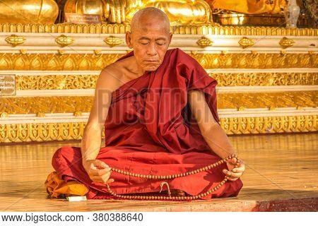 Yangon, Myanmar - December 18th 2017: A Burmese Buddhist Monk Praying In The Evening Sun At The Shwe