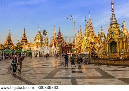 Yangon, Myanmar - December 18th 2017: People Walking Around The Shwedagon Pagoda In The Evening Sun,