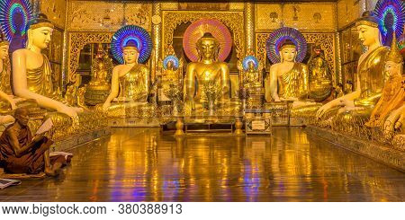 Yangon, Myanmar - December 18th 2017: A Burmese Buddhist Monk Praying Inside A Room With Buddhas At