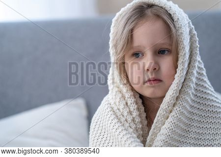 Portrait Small Blonde Girl Wrapped In Blanket, Sitting In Bedroom After Waking Up In Morning. Child