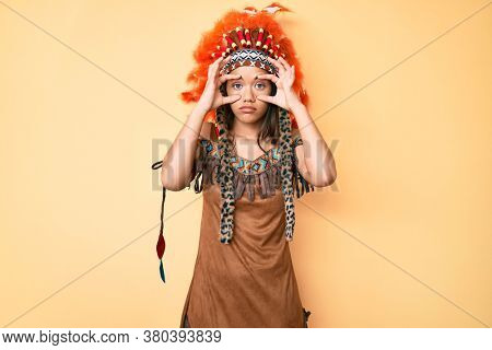 Young beautiful latin woman wearing indian costume trying to open eyes with fingers, sleepy and tired for morning fatigue