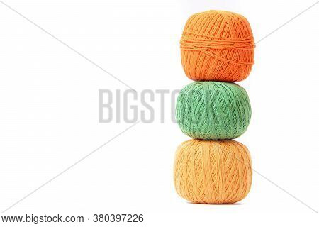 Colored Balls Of Crochet Thread On A White Background . Copy Space. The Tangles Are Arranged In A Co