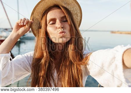 Image of cheerful ginger woman making kiss lips and taking selfie photo while walking on promenade