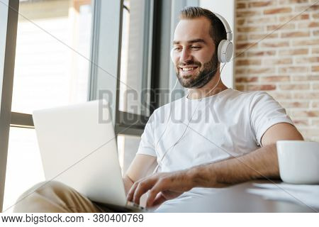 Image of handsome joyful man in headphones smiling and working with laptop while sitting at table in office