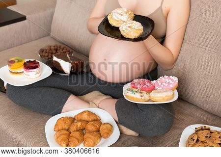 Close Up Of Hungry Pregnant Woman Sitting On The Sofa Is Eating A Lot Of Unhealthy Food Such As Donu