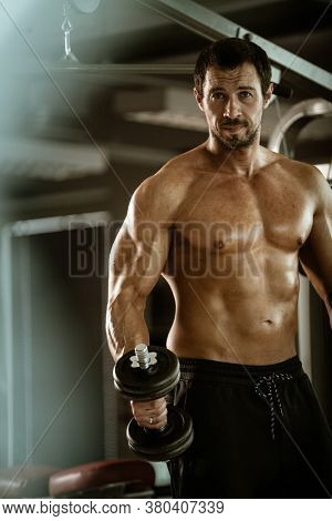 Fitness in gym, sport and healthy lifestyle concept. Handsome athletic man with naked torso making exercises. Bodybuilder male model training biceps muscles with dumbbell.