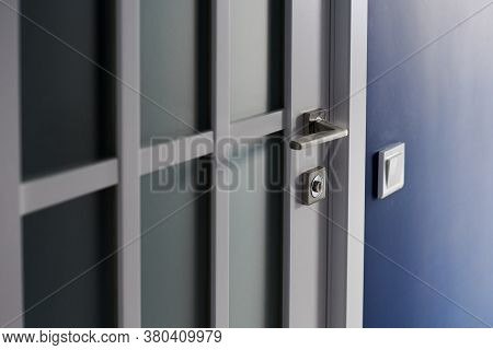 White Interior Door With Handle. Blue Wall In Modern Apartment, Light Switch Nearby. Wooden Closed D