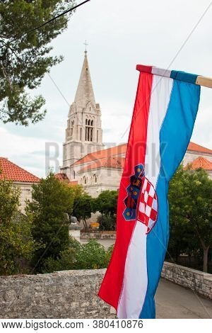 Closeup Of The Croatian Flag Waving In The Wind With The Church In The Village Of Selca, Croatia In
