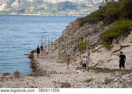 Pusisca, Croatia August 2020 A Group Of Friends Walking Along The Shore Of A Hidden Beach In The For