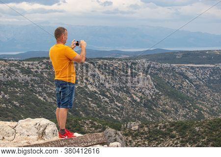 Vidova Gora, Croatia, August 2020 Tourist Standing On The Edge Of The Vidova Gora Mountain And Takin