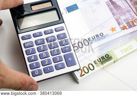 Calculator In The Hand And A Bundle Of Banknotes 500 And 200 Euros