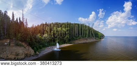 Aerial panorama of the wild beach with sailing vessel on the coast