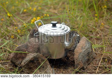 Tourist Teapot On Gas Burner On Grass.