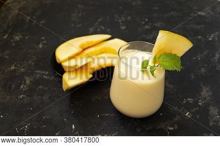 Melon Milk Shake On A Black Background. Ripe Sliced Melon Is Lying Nearby. The Smoothie Glass Is Dec