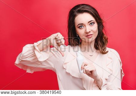 Beautiful Woman Evaluates A Cosmetic Product Holding A Tube With Cream In Her Hands, Studio Photo On