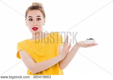 Beautiful Woman In A Bright Yellow T-shirt Refuses The Cake She Is Holding In Her Hands On An Isolat