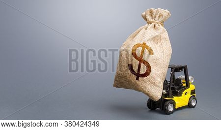 Forklift Carrying A Dollar Money Bag. Anti-crisis Budget. Borrowing On Capital Market. Stimulating E