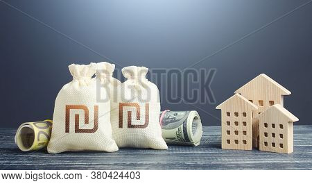 Israeli Shekel Money Bags And Residential Buildings Figures. Financing The Construction Of New Settl