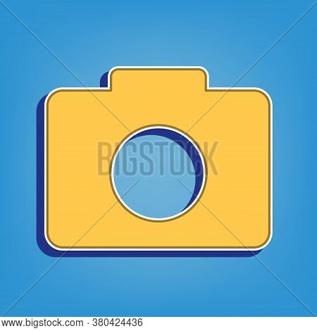 Digital Camera Sign. Golden Icon With White Contour At Light Blue Background. Illustration.