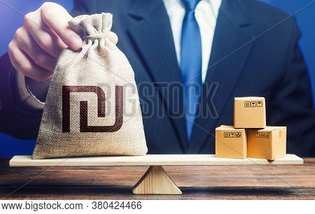 Israeli Shekel Money Bag And Boxes On Scales. Trade Balance And Purchasing Power. Import And Export