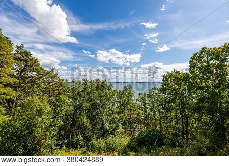 Beautiful Nature Landscape View With View Baltic Sea. Tops Of Green Forest Trees On Blue Sky And Whi