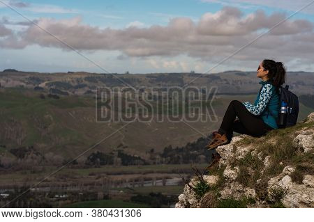 Young Woman Sitting At The Top Of A Mountain And Contemplating The Landscape. Travel Concept